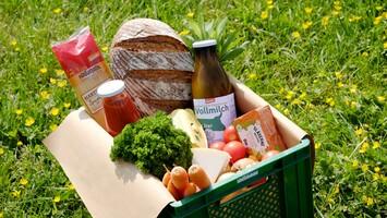 Ökokiste mit Gemüse, Brot, Milch und Naturwaren